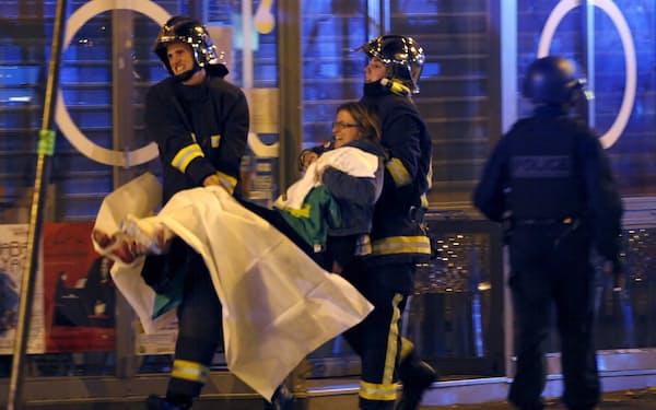 パリ同時テロの負傷者を運ぶ救急隊(15年、パリ・バタクラン劇場近く)=ロイター