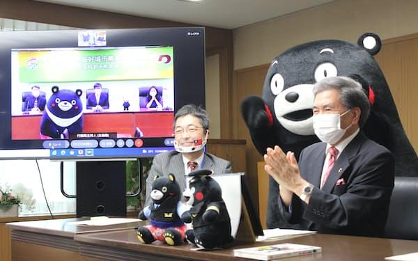 高雄市の陳市長(画面中央)とオンラインで会談する、熊本県の蒲島知事(右、県庁)