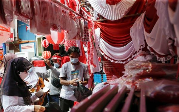 インドネシアなど新興国中銀の多くは、米緩和縮小への備えと景気への配慮の板挟みに直面する(8月、ジャカルタのマーケット)=ロイター