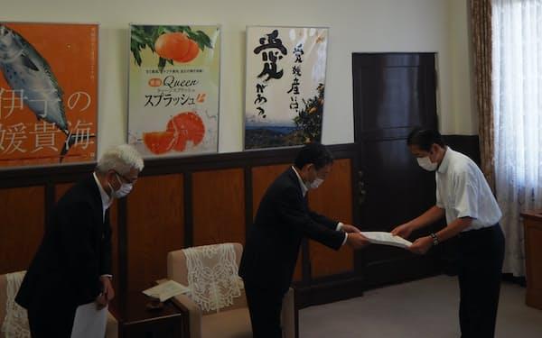 四国電の長井社長(中央)は愛媛県の中村知事(右)に報告書を手渡した(10日、愛媛県庁)