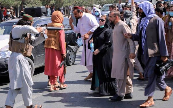 反パキスタンを訴える抗議デモ参加者に銃を向けるタリバンのメンバー(7日、カブール)=ロイター
