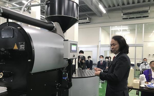 完成した新工場の焙煎機のスイッチを入れる鈴木太郎社長(7日、ひたちなか市)