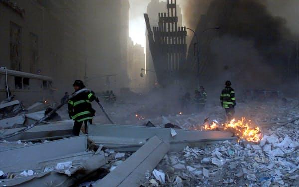 崩壊した世界貿易センタービルと救助活動をする消防隊員=ロイター