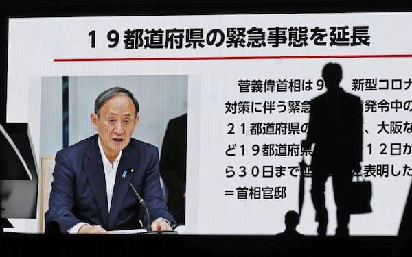19都道府県の緊急事態宣言延長のニュースを伝える東京・秋葉原の大型モニター=共同