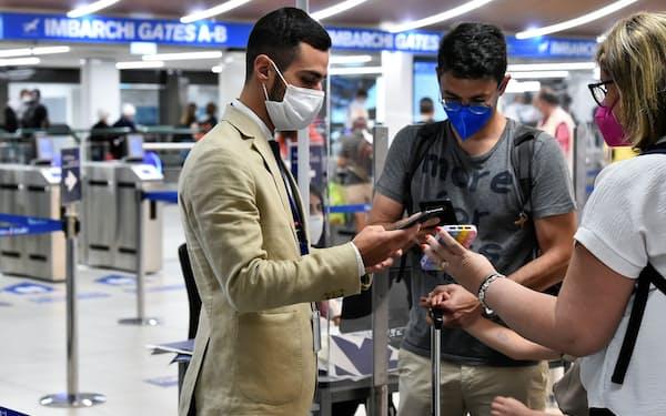 ワクチン接種証明の互換性が課題に(1日、イタリアの空港でデジタル証明書を見せる乗客たち)=ロイター