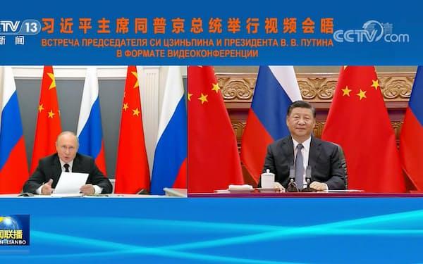 テレビ電話で協議をするロシアのプーチン大統領(左)と中国の習近平国家主席(中国中央テレビの映像から)=共同
