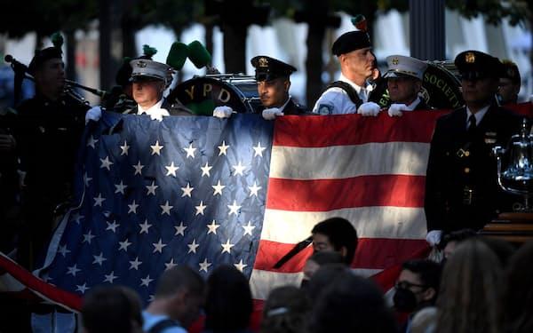 米同時テロ20年の式典で米国旗を掲げるニューヨークの警察官と消防隊員(11日)=ロイター