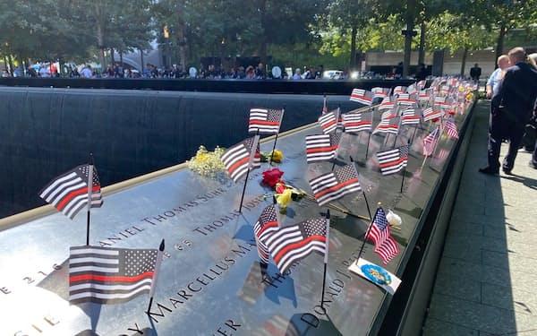 犠牲者の名前を刻んだ石碑には、花やゆかりの品、星条旗が置かれた(11日、ニューヨーク)