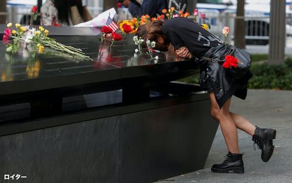 犠牲者の名前が刻まれた碑の前に多くの人たちが足を運び、悲しみを新たにした(11日、ニューヨーク)=ロイター