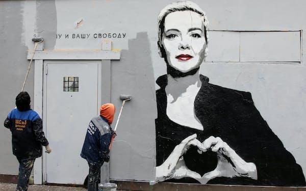 壁に描かれたベラルーシ反体制派コレスニコワ氏の絵を消す作業員(9月8日、ロシア・サンクトペテルブルク)=ロイター