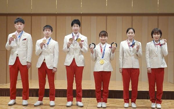日本卓球協会の東京五輪報告会で、メダルを手にポーズをとる(左から)張本智和、丹羽孝希、水谷隼、伊藤美誠、石川佳純、平野美宇(12日、東京都内)=共同