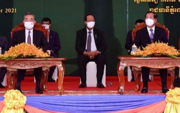 新国立競技場の引き渡し式に出席する中国の王毅外相㊧とカンボジアのフン・セン首相㊨(12日、プノンペン)