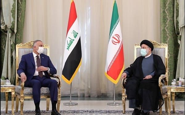12日、テヘランで会談するイランのライシ大統領(右)とイラクのカディミ首相=イラン大統領府提供・ロイター