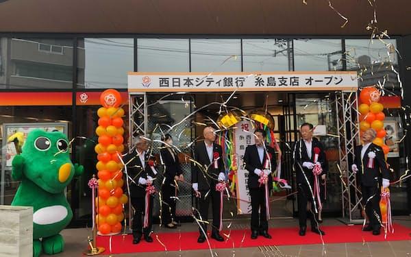 糸島支店開店を記念し、テープカットする関係者(13日、福岡県糸島市)