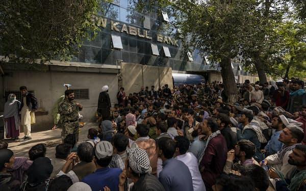 現金を引き出そうと大勢の市民が銀行の前に集まった(12日、カブール)=AP