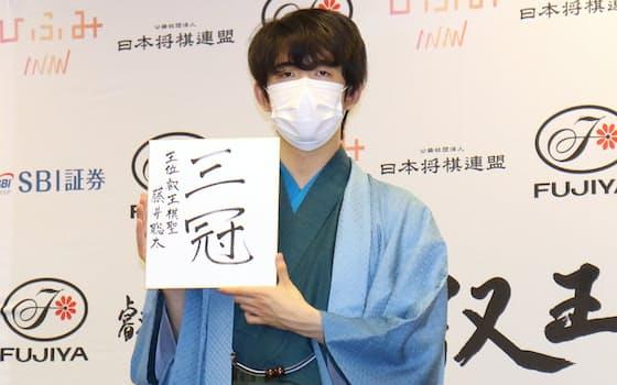 最年少記録を更新し、記者会見で色紙を掲げる藤井聡太三冠(13日、東京都渋谷区)