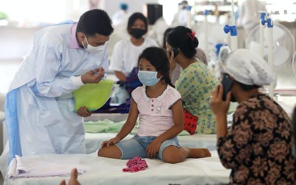インド・ニューデリーで、新型コロナウイルス感染が疑われる子どもを診察する医師=共同