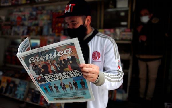 「政府に逆境」と書かれた新聞を読む市民(13日、ブエノスアイレス)=ロイター