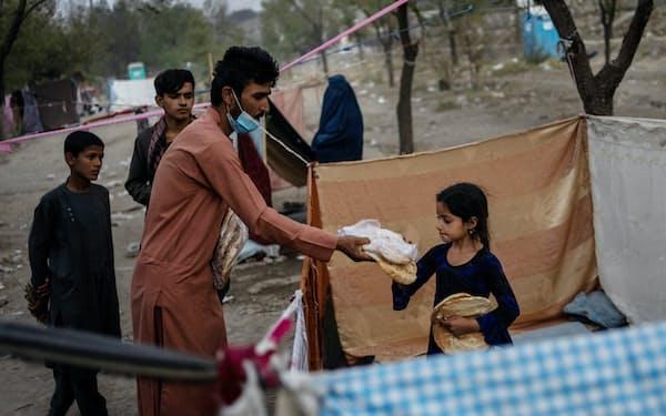 アフガンの国内避難民キャンプで食料を受け取る少女(13日、カブール)=AP
