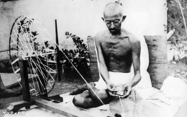 サバルマティ・アシュラムで手紡ぎ車を回すガンジー(1925年)=ゲッティ共同