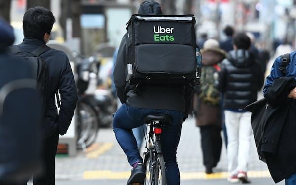 街中を自転車で走るウーバーイーツの配達員(東京・新宿)