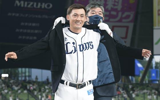 通算2千安打達成のセレモニーで野茂英雄氏(右)から名球会のブレザーを贈られる西武・栗山=メットライフドーム(共同)
