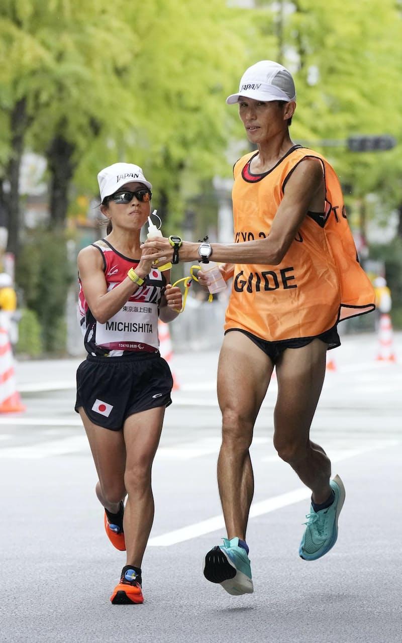 女子マラソン(視覚障害T12) 35キロ付近を給水しながら力走する道下美里(左)=東京都内