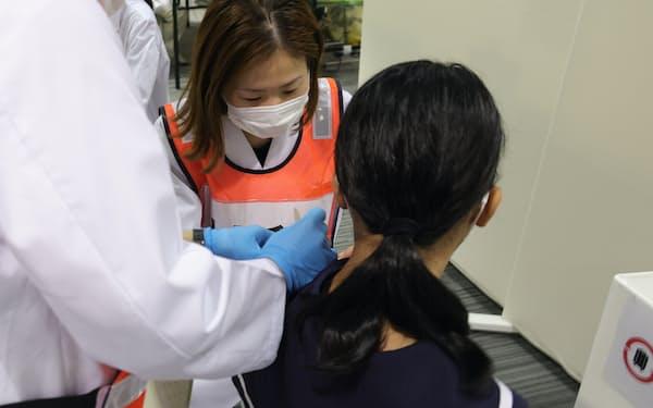 新型コロナウイルスワクチンの接種を受けに訪れた中学生(手前)=名古屋市中区