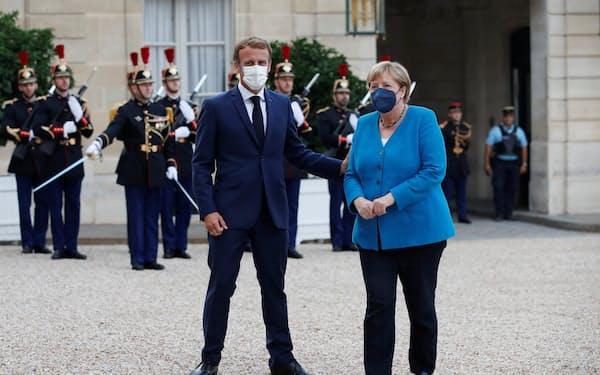 16日、メルケル首相㊨は独総選挙後の政治空白長期化を防ぎたいと語った(パリ)=ロイター