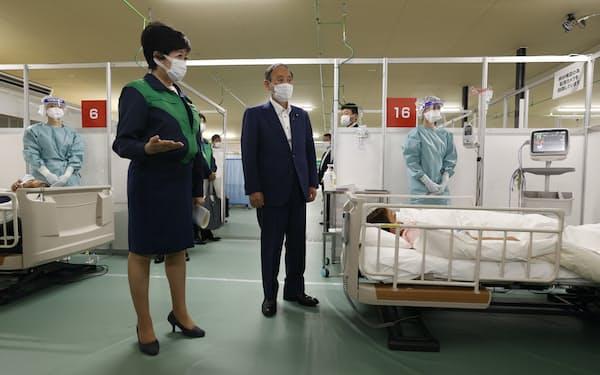 「酸素・医療提供ステーション」を視察する菅首相(中央)。手前左は東京都の小池知事(16日、東京都中央区)=代表撮影