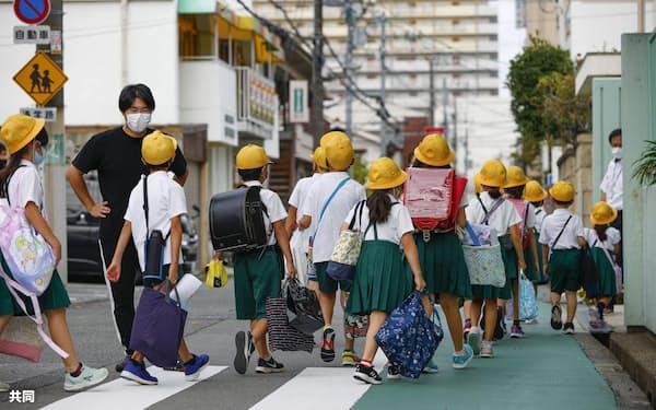 新学期が始まり、集団登校する児童ら(8月、大阪市)=共同