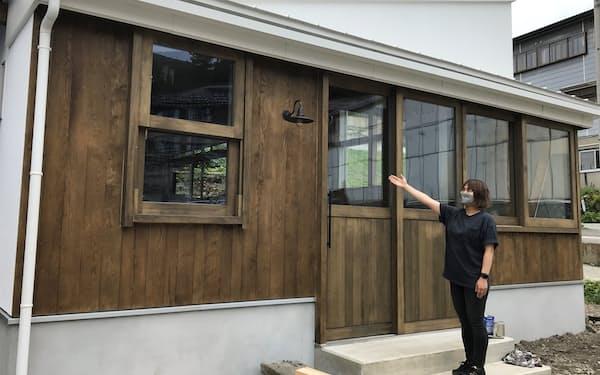外壁は湯50のメンバーが塗って仕上げた(完成間近の店舗を紹介する佐藤さん、山形市)