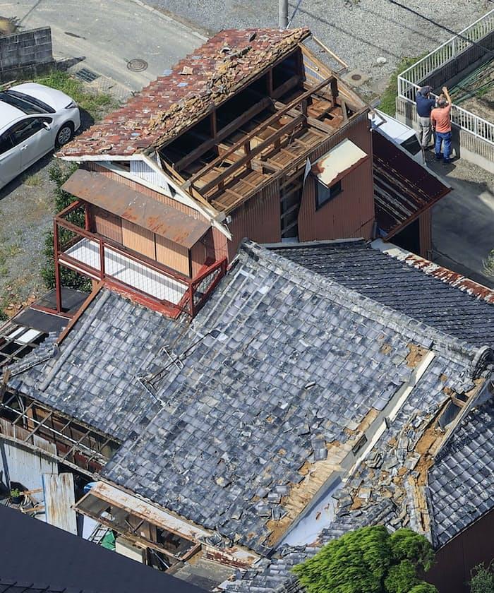 台風14号の影響とみられる突風で屋根の瓦などが飛ばされた建物(18日午後、和歌山県美浜町)=共同