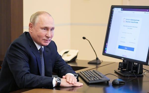 17日、モスクワ郊外の公邸で遠隔操作でロシア下院選の電子投票をするプーチン・ロシア大統領=AP