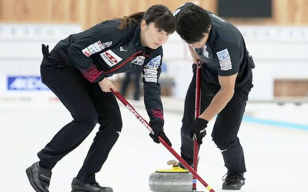 決定戦第1試合でスイープする松村千(左)、谷田組(20日、稚内市みどりスポーツパーク)=共同
