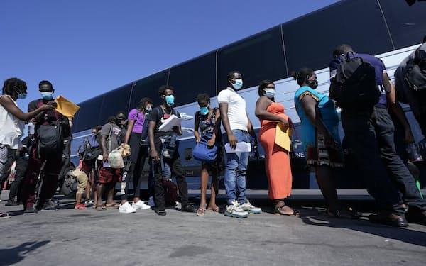 20日、米南部テキサス州デルリオでバスに乗る移民=AP