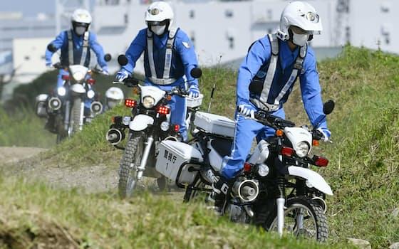 秋の全国交通安全運動開始に合わせ、災害現場の状況を確認するオフロード用の白バイで訓練する警視庁の隊員(21日、東京都江東区)=共同