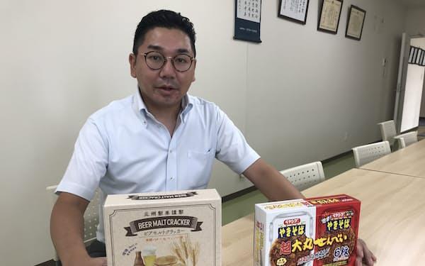 「ビアモルトクラッカー」㊧と「ペヤングやきそば味 超大丸せんべいハーフ&ハーフ箱」を持つ三州製菓の斉之平一隆社長