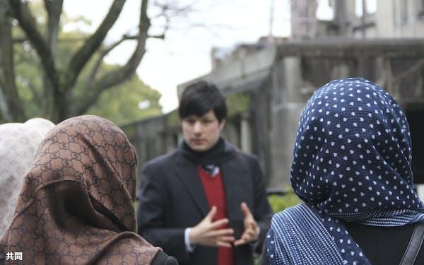 広島市の原爆ドーム前で、ユニタールの職員(奥)から話を聞くアフガニスタンの女性たち(手前、2018年)=共同
