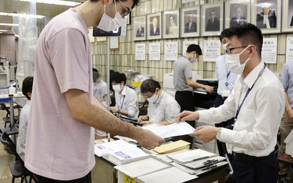接種証明書を受け取る様子(東京都品川区役所)=共同