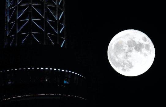 夜空に輝く「中秋の名月」。左は東京スカイツリー(21日、東京都内)
