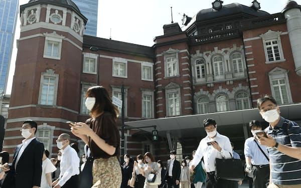 マスク姿で出勤する人たち(18日午前、東京・丸の内)