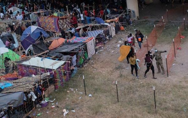 22日、米南部テキサス州デルリオに滞在する移民=ロイター