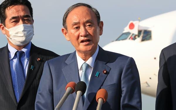 米国への出発を前に記者の質問に答える菅首相(23日、羽田空港)