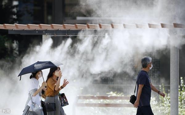 日傘を差したり、設置されたミストシャワーの近くを歩いたりして、暑さをしのぐ人たちの姿が見られた(23日午後、東京・銀座)=共同