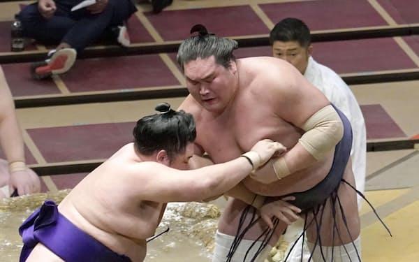 明生(左)が下手投げで照ノ富士を破る(23日、両国国技館)=共同