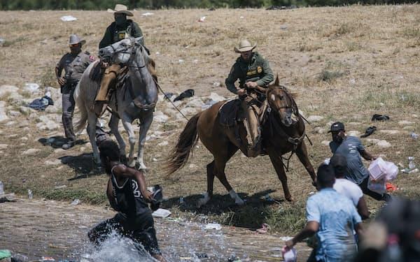 馬に乗って移民を威嚇する国境警備隊員(19日、米南部テキサス州テルリオ)=AP