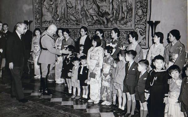 日本人の子供の顔をなでるイタリアの独裁者ムッソリーニ=井上まゆみさん提供(中央の着物姿右側の少女が井上さん)