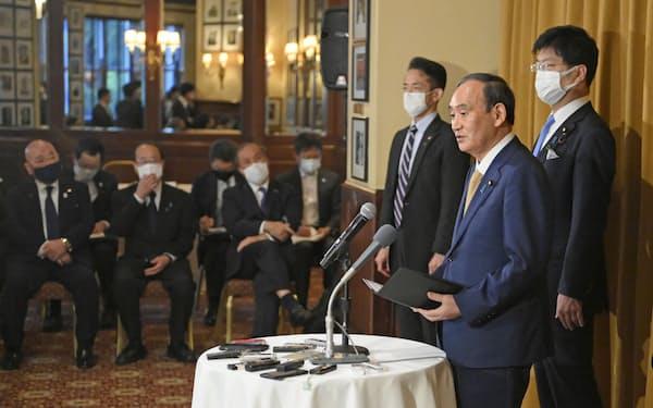 日米豪印首脳会議などを終え、記者団の質問に答える首相(24日、ワシントン)=共同