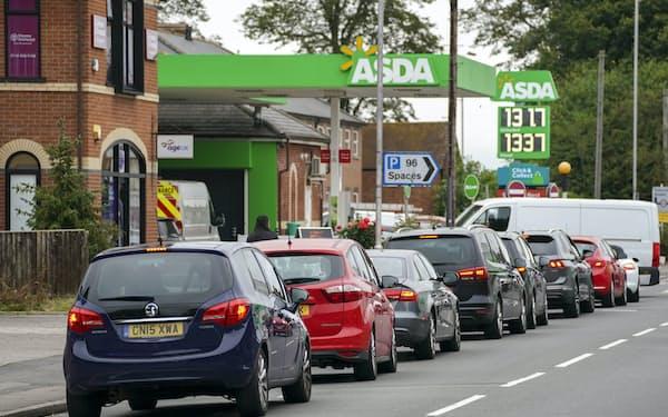 トラックの運転手不足で一部ガソリンスタンドが閉鎖したことを受け、給油のために長蛇の列ができた(25日、レディング)=AP